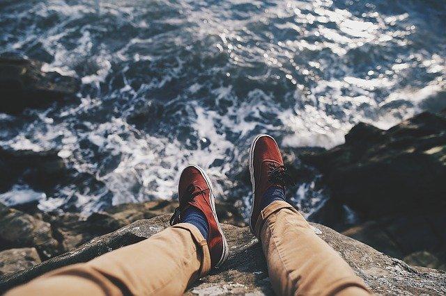 Osoba sediaca na skale so spustenými nohami