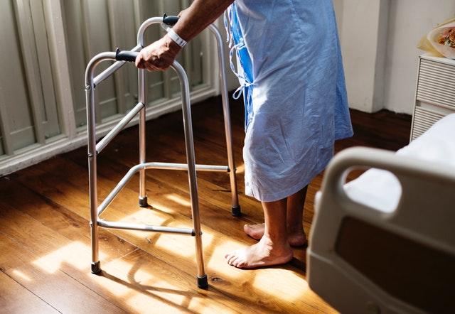 Človek v nemocničnej izbe s chodítkami