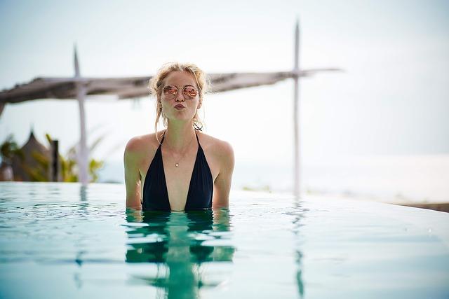 Žena posielajúca bozk v okuliaroch stojaca v bazéne.jpg