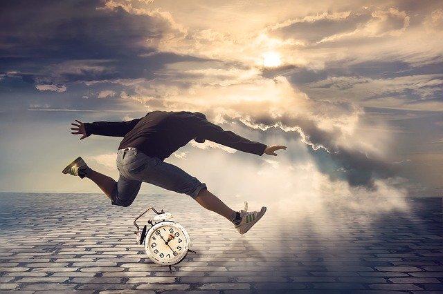 Abstraktný obrázok ako muž skáče cez hodiny v oblakoch.jpg