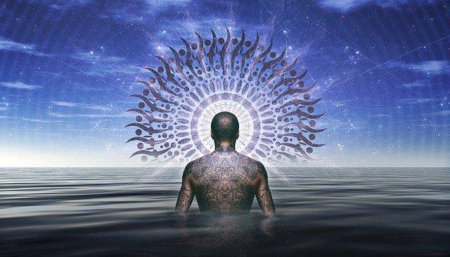 Muž s výrazným tetovaním na chrbte kráča vo vode.jpg