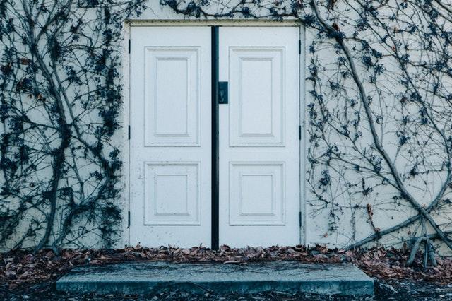 Biela stena obrastená rastlinami s bielymi dverami z dreva.jpg