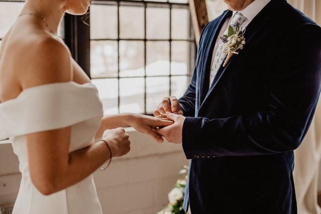 Ženích dáva neveste na ruku prsteň.jpg