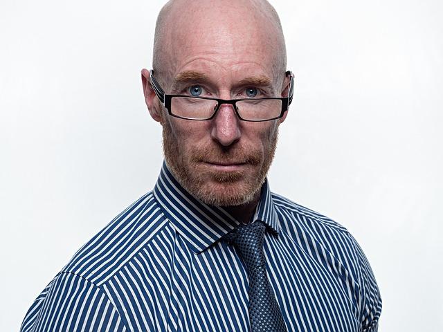 Starší muž s bradou a s dioptrickými okuliarmi v pásikovej bielo-modrej košeli.jpg