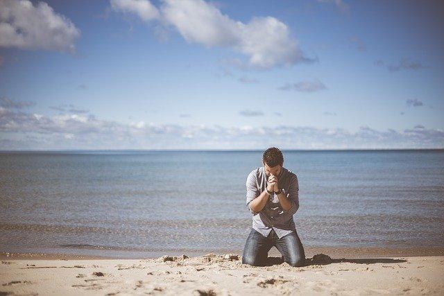 Muž sa modlí na pláži pri mori