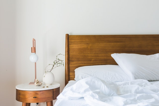 Posteľ s dreveným čelom a bielymi posteľnými obliečkami