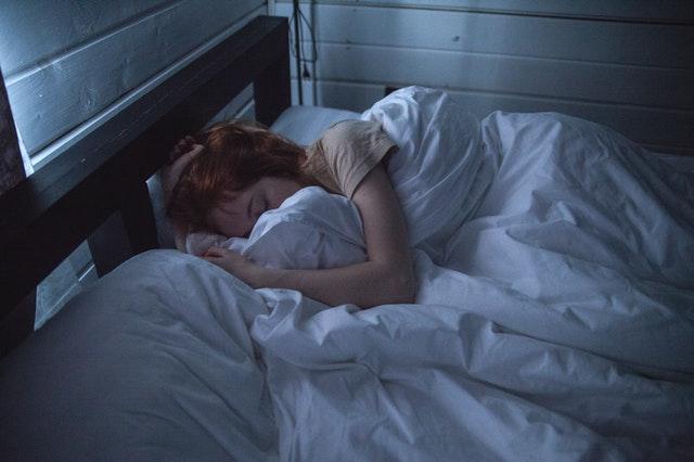 Žena s ryšavými vlasmi leží zakrytá paplónom v posteli
